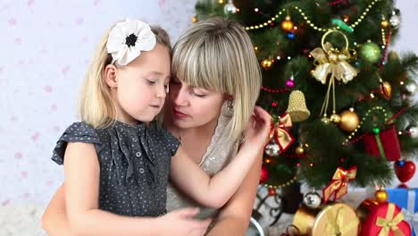 Mother-Kisses-Her-Daughter-Sitting-On-The-Floor-Near-The-Christmas-Tree