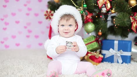 Newborn-In-Santa-Hat-Beside-A-Christmas-Tree
