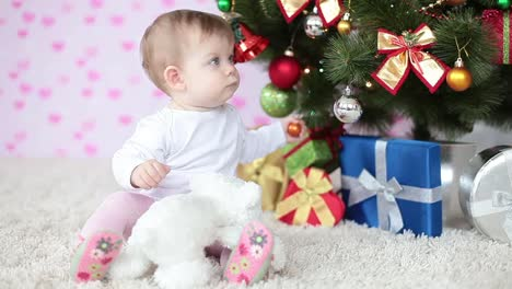 Newborn-Near-A-Christmas-Tree-Sitting-On-The-Floor