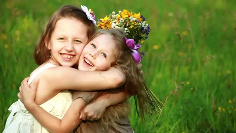 Sisters-Hugging-While-Sitting-In-The-Grass