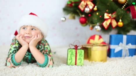 Smiling-Girl-In-Santa-Hat-Lying-Near-The-Christmas-Tree