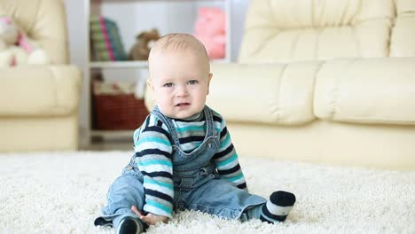 Baby-Boy-Sitting-On-The-Carpet-In-The-Room