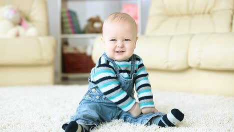 Baby-Boy-Sitting-On-The-Floor-And-Smiling