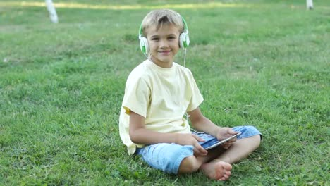 Boy-Listening-Música-Through-Headphones-Using-A-Tablet-PC