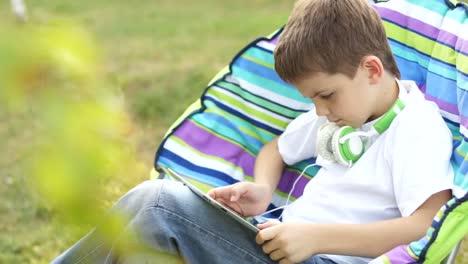 Chico-En-Línea-Con-Un-Tablet-Pc-Sentado-En-Una-Silla-Al-Aire-Libre