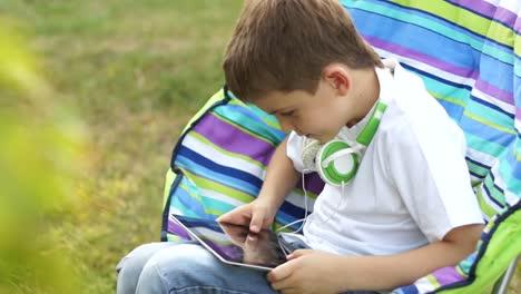 Niño-Jugando-Con-Un-Tablet-Pc-Al-Aire-Libre