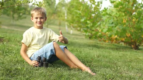 Boy-Watching-With-Binoculars-Sitting-On-The-Grass-Thumbs-Up-Ok