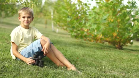 Boy-Watching-With-Binoculars-Sitting-On-The-Grass