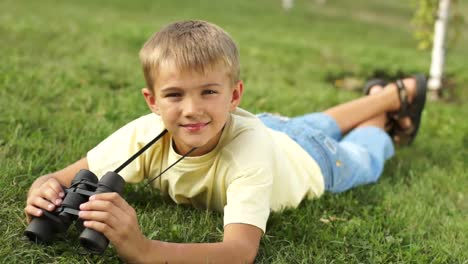 Boy-With-Binoculars-Lying-On-The-Grass