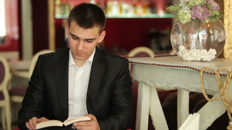 Businessman-Reading-A-Book-And-Smiling-At-The-Camera