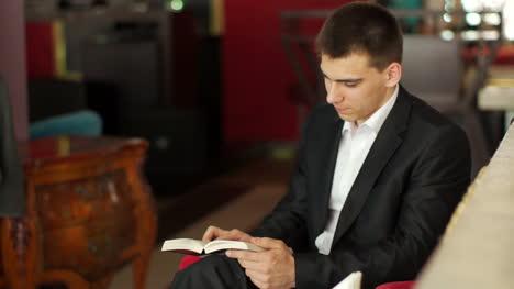 Empresario-Leyendo-Un-Libro-Y-Sonriendo-En-Café