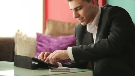 Geschäftsmann-Tippt-Auf-Einem-Tablet-Und-Lächelt