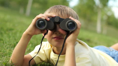 Closeup-Portrait-Of-A-Boy-Looking-Through-Binoculars-At-Camera
