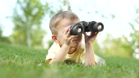 Closeup-Portrait-Of-A-Little-Boy-Looking-Through-Binoculars-Outdoors