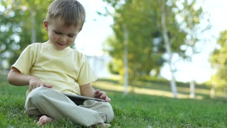Cute-Boy-Using-A-Tablet-Computer-Outdoors