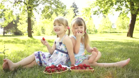Funny-Girls-Eating-Strawberries-Sitting-On-The-Grass