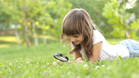 Girl-With-Magnifier-Lying-On-The-Grass