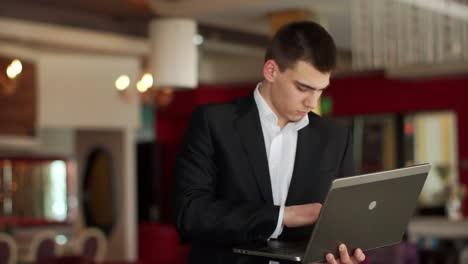 Chico-De-Pie-En-La-Cafetería-Con-Laptop-Y-Escribiendo