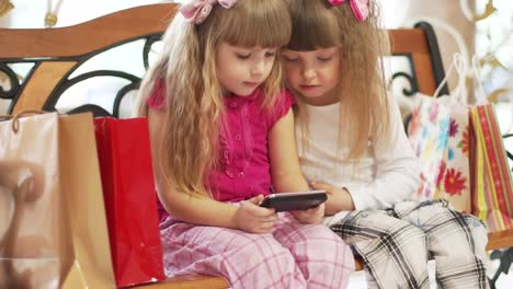 Happy-Children-Sitting-On-The-Bench-Playing-With-The-Phone