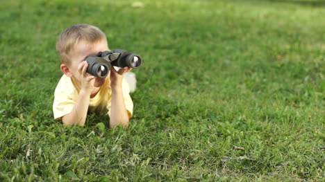 Little-Boy-With-Binoculars-Lying-On-The-Grass