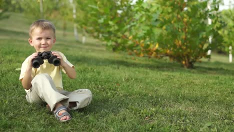 Little-Boy-With-Binoculars-Sitting-On-The-Grass-Outdoors-Thumbs-Up-Ok