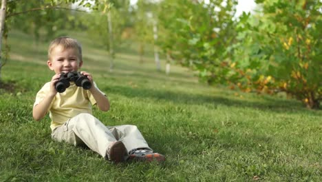 Little-Boy-With-Binoculars-Sitting-On-The-Grass-Thumbs-Up-Ok