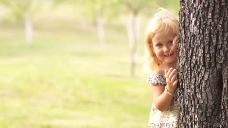 Little-Girl-Hiding-Behind-A-Tree