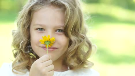 Little-Girl-Smelling-A-Daisy-Flower-In-The-Meadow