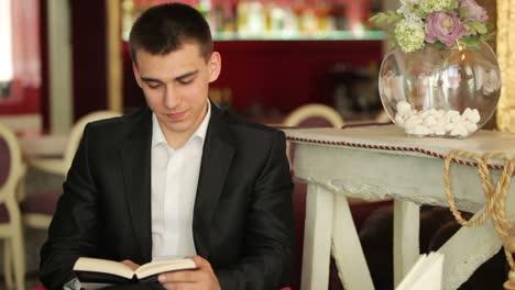Hombre-Leyendo-Un-Libro-Y-Sonriendo-En-Café