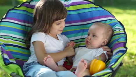 Newborn-Baby-And-His-Sister-Sitting-In-A-Chair-Outdoors-With-Vegetables