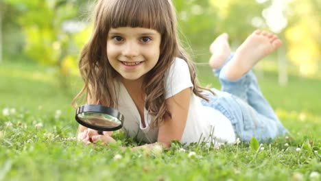 Portrait-Child-With-Magnifier-Lying-On-The-Grass