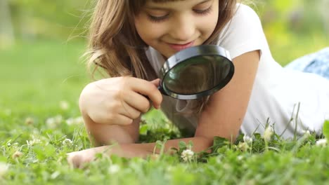 Portrait-Girl-With-Magnifier-Lying-On-The-Grass-Outdoors
