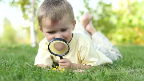 Portrait-Of-A-Little-Boy-With-A-Magnifier-And-Lying-On-The-Grass