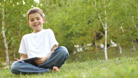 Schoolboy-With-A-Tablet-PC-And-Sitting-On-The-Grass-Thumbs-Up-Ok