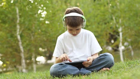 Schoolboy-With-A-Tablet-PC-Emotional-Listening-To-Music