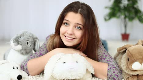 Smiling-Teenagers-Lying-On-The-Floor-With-Plush-Rabbit