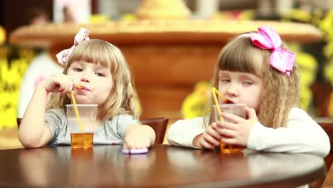 Two-Girls-Drinking-Juice-And-Looking-At-Camera