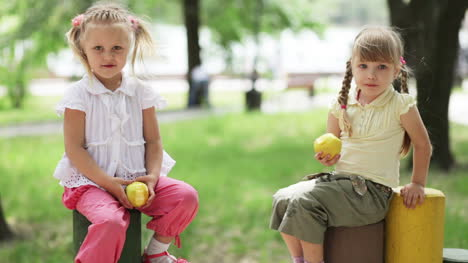 Two-Girls-Eating-The-Apples-In-The-Playground