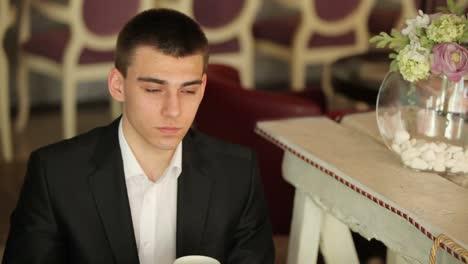 Junger-Erwachsener-Der-Kaffee-In-Einem-Café-Trinkt-Und-In-Die-Kamera-Schaut