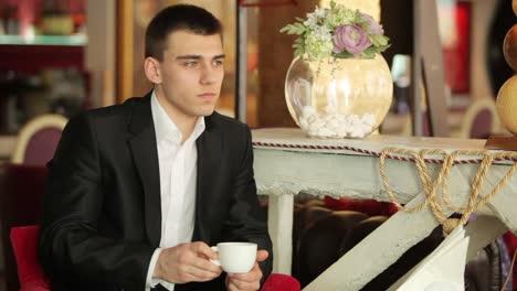Junger-Erwachsener-In-Einem-Anzug-Der-In-Einem-Café-Kaffee-Trinkt-Und-In-Die-Kamera-Schaut