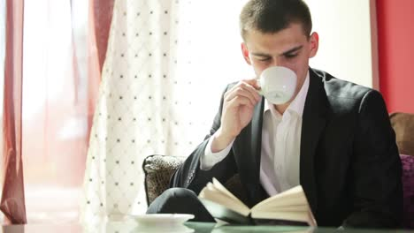 Young-Businessman-Drinking-Coffee-And-Reading-A-Book