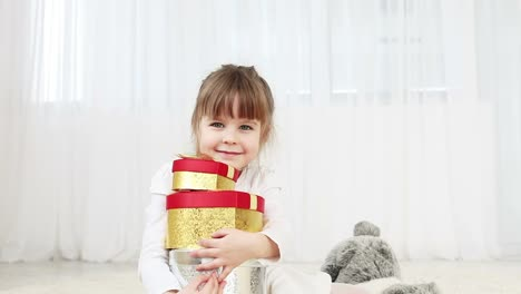 Junges-Mädchen-Mit-Geschenken-Auf-Dem-Boden