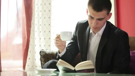 Young-Guy-Reading-A-Book-And-Drinking-Coffee