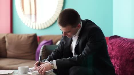 Chico-Joven-Sentado-En-La-Cafetería-Y-Escribiendo-En-Un-Cuaderno