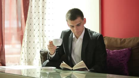 Young-Man-Drinking-Coffee-And-Reading-A-Book
