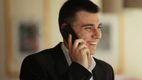 Young-Man-Speaking-By-Phone-And-Laughing