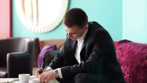 Joven-Escribiendo-En-Un-Cuaderno-Y-Mirando-Por-La-Ventana