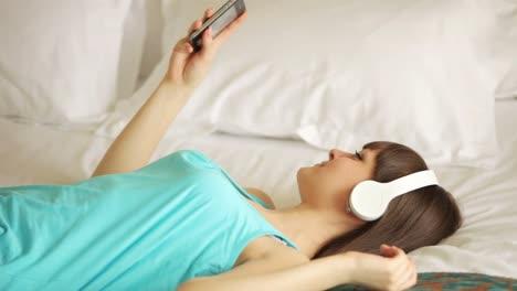 Junge-Frau-Hört-Musik-Auf-Dem-Bett