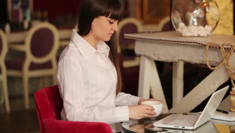 Young-Woman-Typing-And-Drinking-Coffee