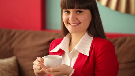 Young-Woman-With-Cup-Of-Coffee-Smiling-At-Camera